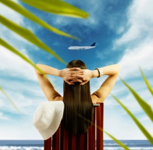 Young woman watching airplane fly by from tropical beach
