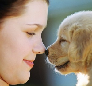 Woman Rubbing Noses with Puppy