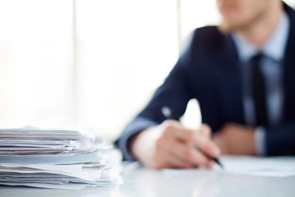 Stack of documents at workplace and male employee on background